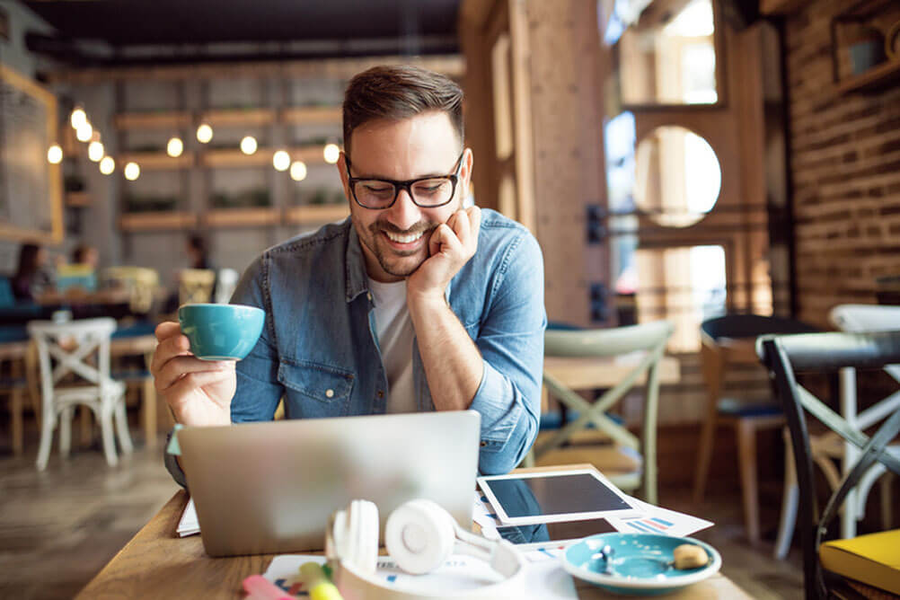Man drinking coffee and smiling at computer screen